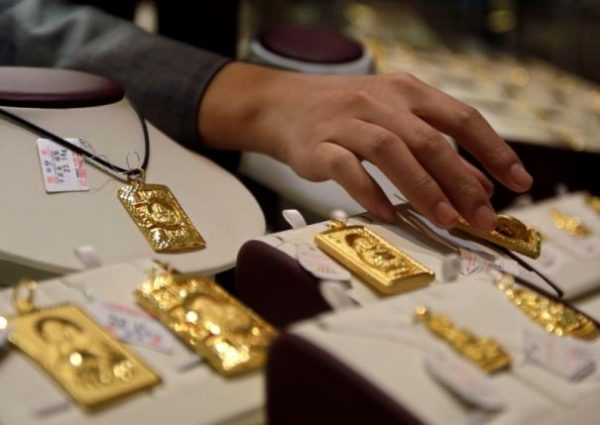 File picture shows a sales assistant putting back a gold Buddha-shaped pendant after showing to a customer at Caibai Ornaments store in Beijing